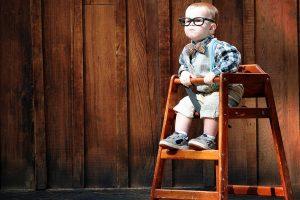mały filozofi siedzi na wysokim krzesełku na tle drewnianej ściany